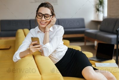 Young happy business woman chatting by mobile phone