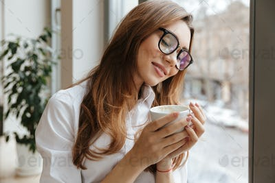 Cute business woman sitting in cafe drinking coffee
