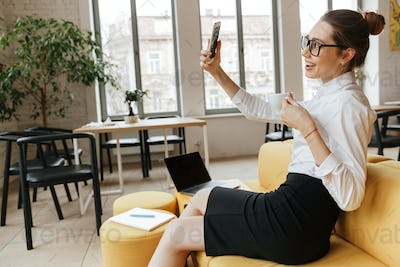 Excited business woman make selfie by mobile phone
