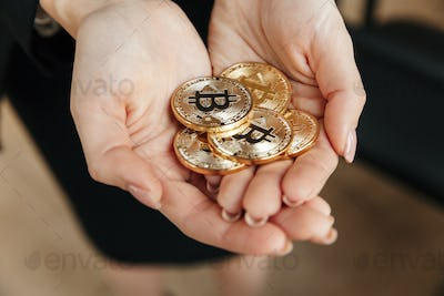 Business lady showing her bitcoins in hands.