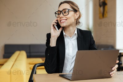 Cheerful business woman talking by mobile phone