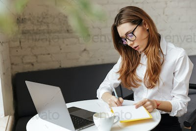 Thoughtful business woman indoors using laptop