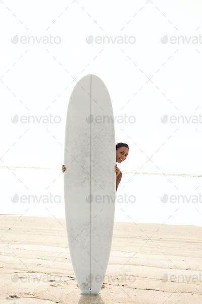 beautiful happy joyful girl or woman on sunny sandy beach playing with surfboard