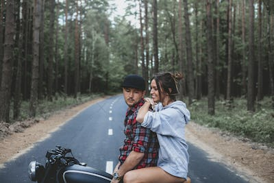 handsome young man and woman travelling together on motorbike