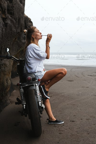 thursty young girl sitting on the motorbike and drinking water