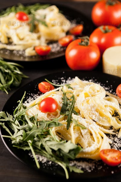 Plate with tagliatelle pasta, cherry tomatoes and greenery