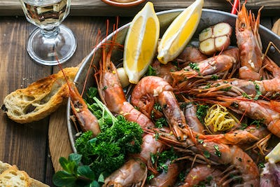 Tasty shrimps with garlic, lemoc, bread and wine