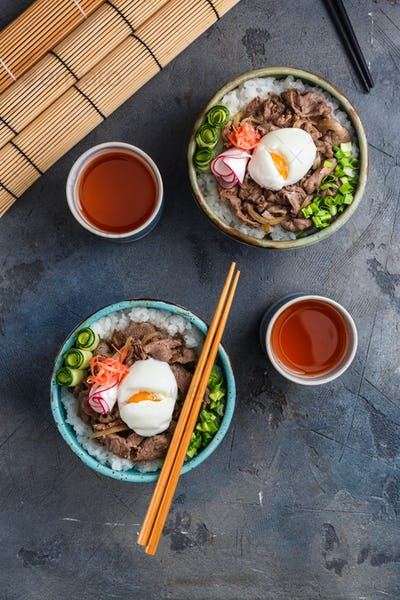 Two beef bowls or gyudon with egg and onion top view