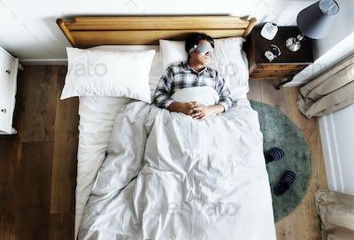 Japanese man sleeping on bed with eye mask