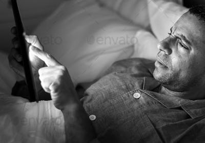 Man using phone on a bed