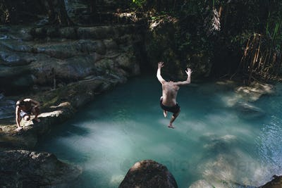Man jumping into a natural pond