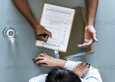 Aerial view of doctor writing patient daily report checklist