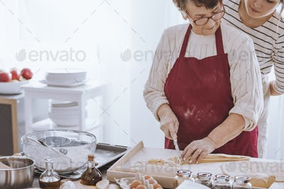 Grandmother concentrating on cutting dough