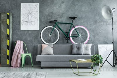 Black bike on grey sofa