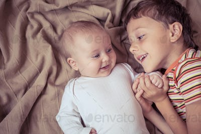 little boy playing with newborn on the bed