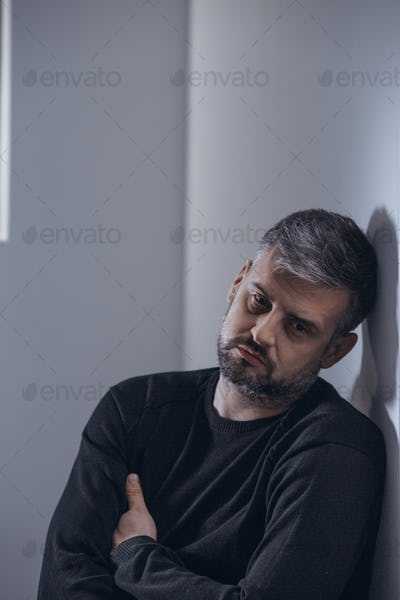 Sad man leaning against wall