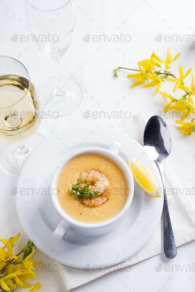 Creamy soup with seafood and lemon on a white background.