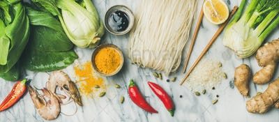 Flat-lay of Asian cuisine ingredients over grey marble background