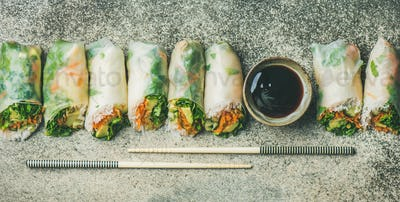 Vegan spring rice paper rolls over concrete background, wide composition