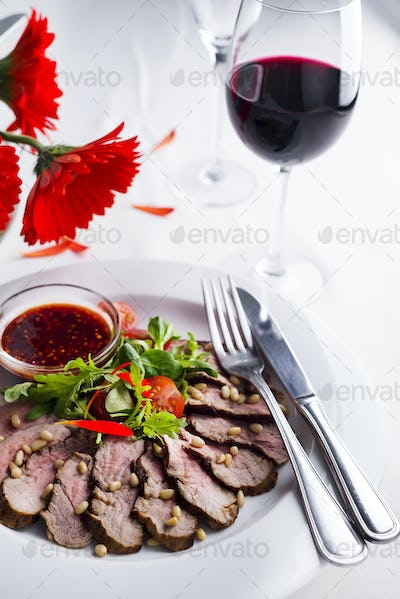 Duck breast roasted with tomato, baby spinach with berry sauce on a white plate