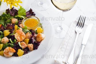 Tropical salad with prawns, lettuce, oranges and mango served on a plate with orange mustard sauce