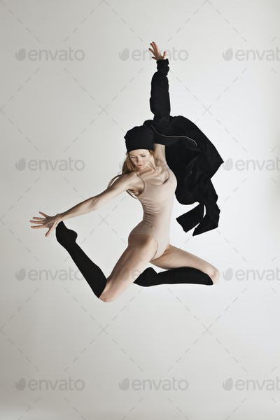 Young beautiful dancer in beige swimsuit dancing on gray background