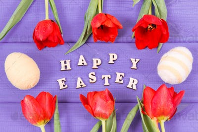 Inscription Happy Easter, tulips and eggs wrapped woolen string on boards, festive decoration