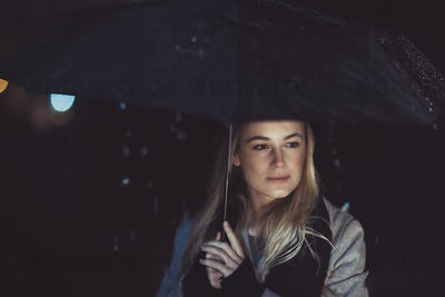 Thoughtful woman outdoors on rainy night