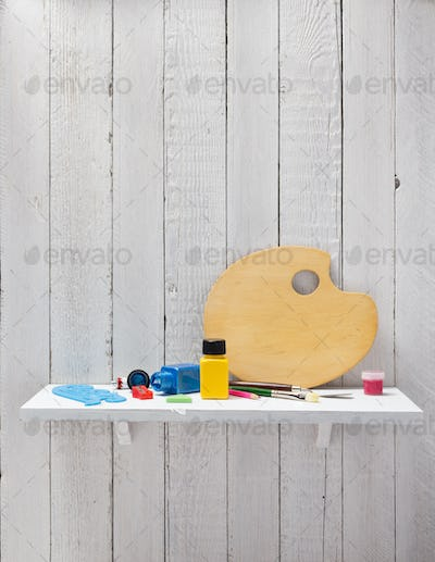 paints and palette on wooden shelf