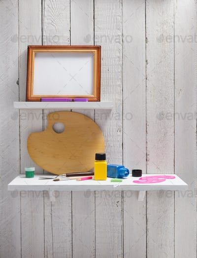 picture frame and paints on wooden shelf