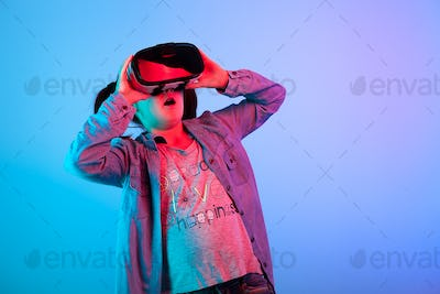 Young girl watching a movie on VR headset