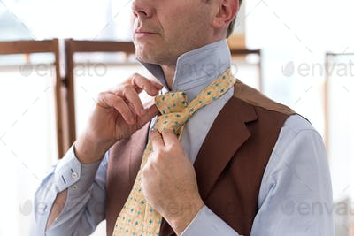 Man knotting his necktie while dressing