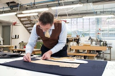 Tailor laying out paper patterns on blue fabric