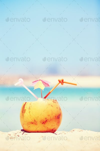Coconut with colorful umbrella and two straws on a beach.