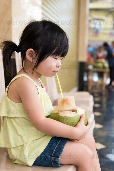 Cute girl drinking coconut water