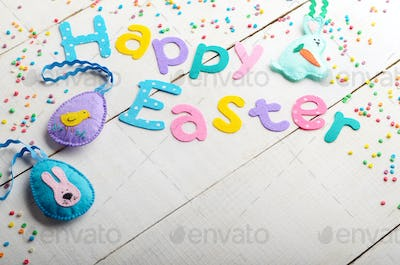 Happy Easter phrase made of fabric letters on white table