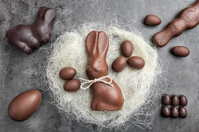 Chocolate Easter bunny and eggs in a nest on rustic background
