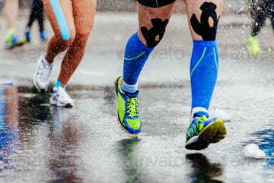 legs runner in compression socks and kinesiology tape on knees running on water