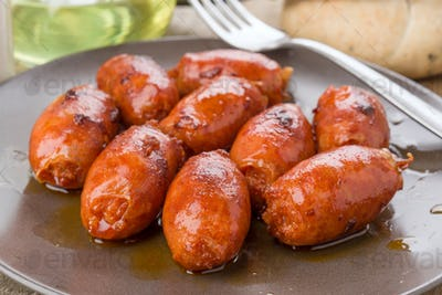 grilled sausage on brown porcelain dish on natural wood