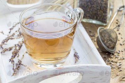 Herbal lavender tea in glass cup with lavender flowers on wooden tray, horizontal
