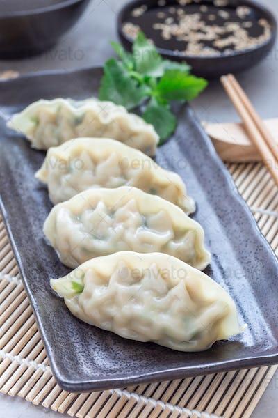 Steamed Korean dumplings Mandu with chicken meat and vegetables on black plate, vertical