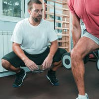 Peronal trainer with male client in the gym