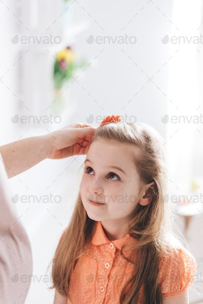 Mother fixing her young daughter's hair