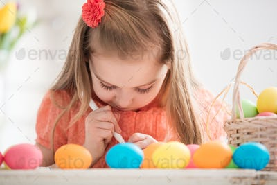 Focused child creating drawings on colorful dyed eggs