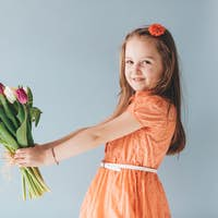 Girl holding a bunch of colorful tulips.