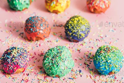 Colorful donuts with sugar strands on a messy background