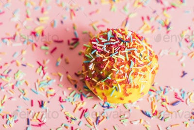 Sprinkled yellow doughnut on pink background.