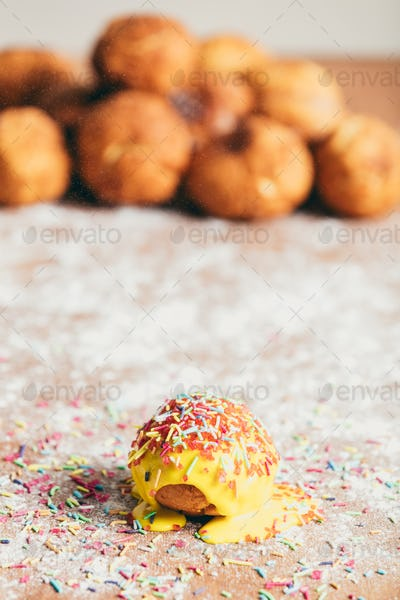Yellow doughnut decorated with sugar strands