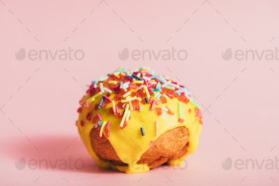 Little round yellow doughnut with colorful sprinkles