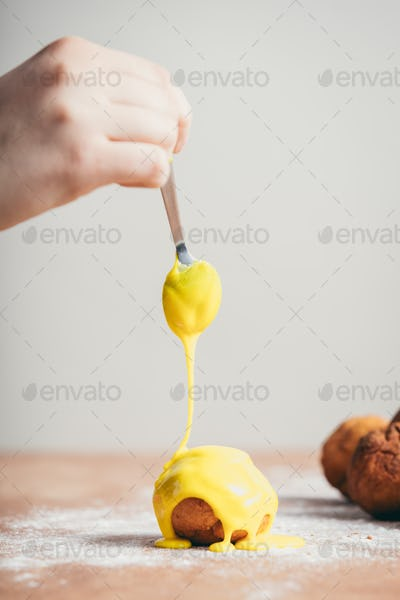 Woman's hand coating a doughnut with yellow frosting.